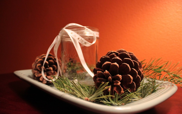 pinecones and candle on dish